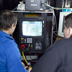 An ROV pilot and assistant prepare the control system as the ROV is lowered into the sea © G. Newman (2005).
